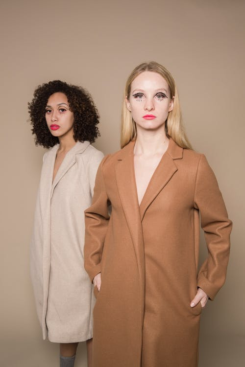 Confident women models with creative makeup in trendy coats standing in studio and looking at camera against beige background
