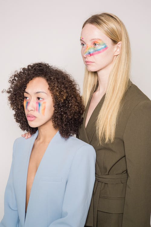 Serious multiethnic women models with multicolored makeup as symbol of LGBTQ and stylish clothes pensively looking away against beige background