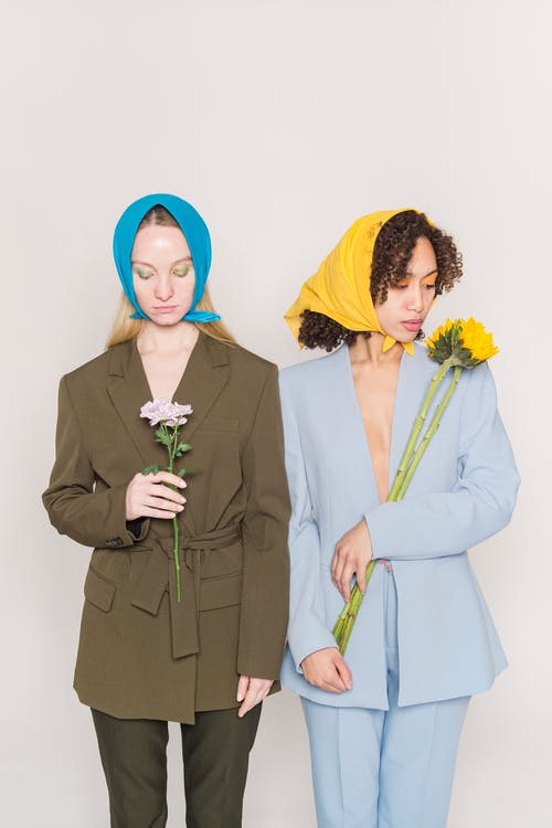 Multiethnic women in colorful stylish outfits standing with flowers