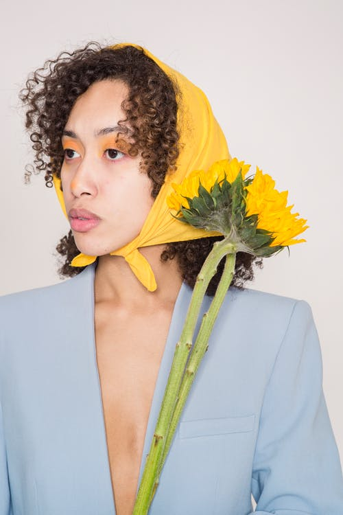 Serious ethnic female model with curly hair in yellow headscarf standing with blooming sunflower and looking away against light background in studio