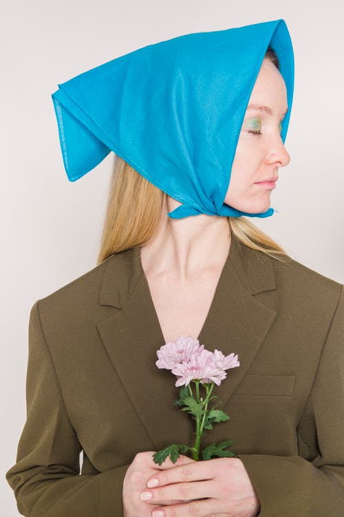 Calm female in blue headscarf standing with flower against light background