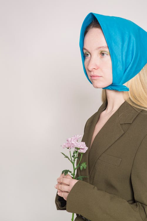 Serious woman in headscarf with flower in hands in studio