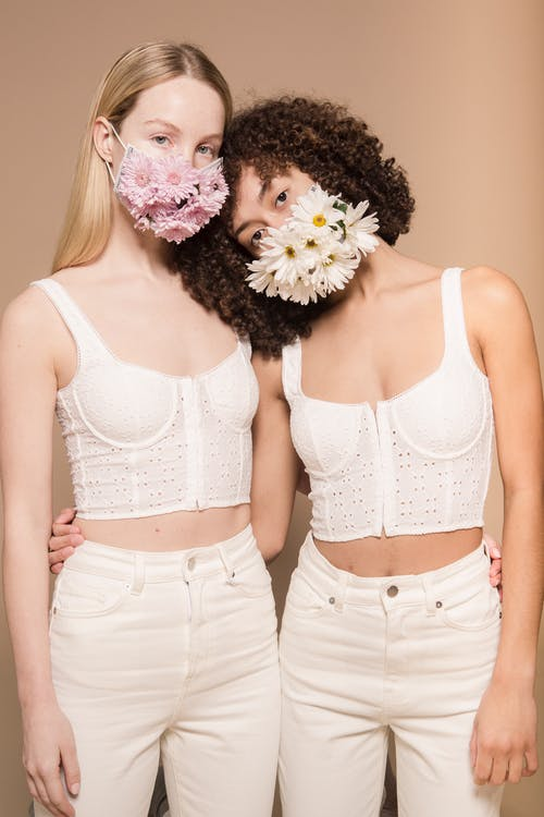 Multiracial friends in protective masks with flowers and white trousers