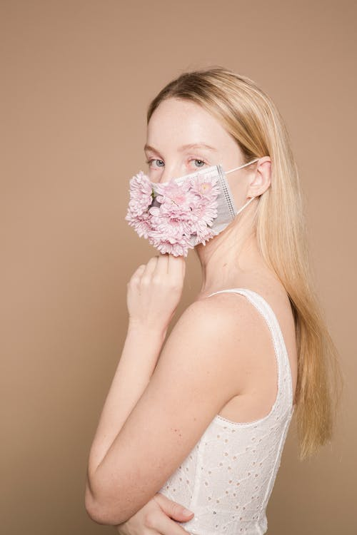 Gentle woman in protective mask with flowers in blossom