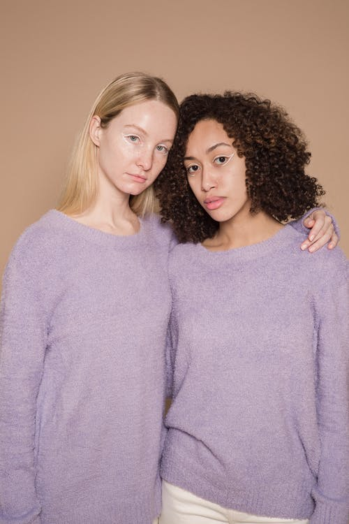 Diverse trendy friends in stylish purple warm sweaters looking at camera on beige background