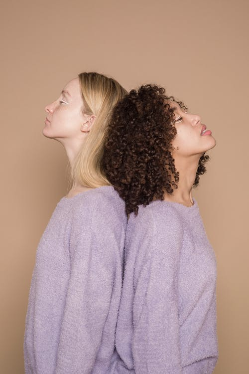 Side view of diverse exhausted friends with extraordinary makeup on beige background of studio