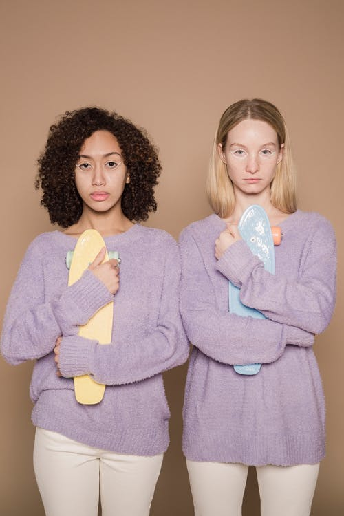 Multiethnic women with pastel longboards in studio