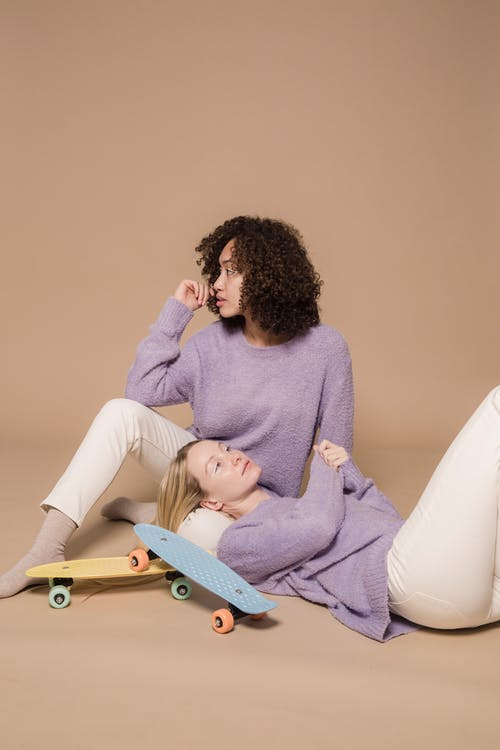 Dreamy diverse friends in white trousers and purple soft sweaters sitting in studio with colorful board on beige background
