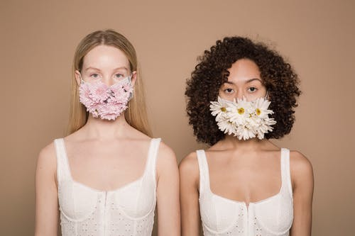 Multiracial women with flowers on protective masks