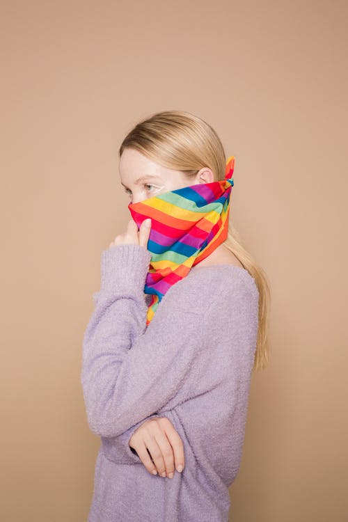 Side view of thoughtful female wearing warm purple pullover and bright multicolored facial scarf on beige background