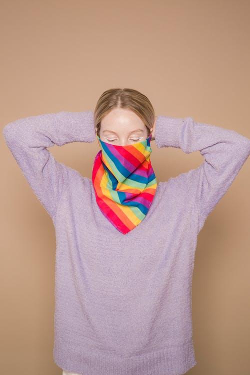 Woman in bright rainbow facial scarf