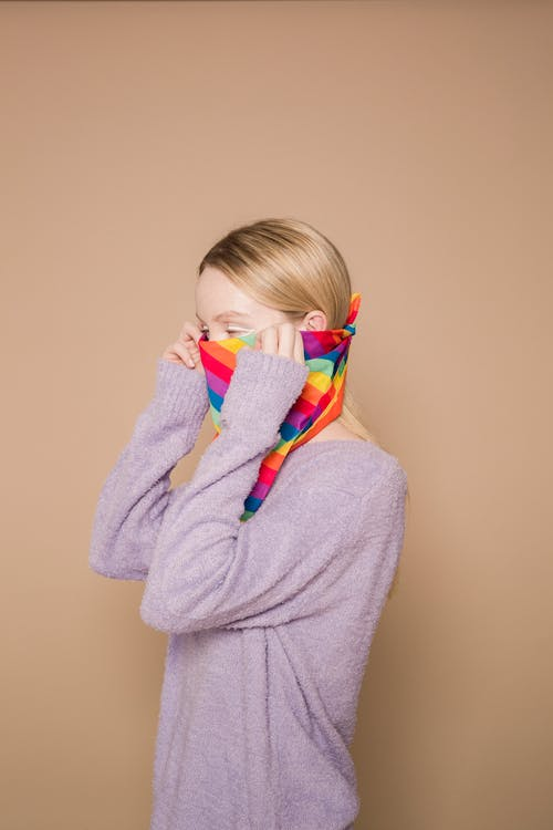 Woman in sweater covering face with rainbow bandana in bright studio on beige background