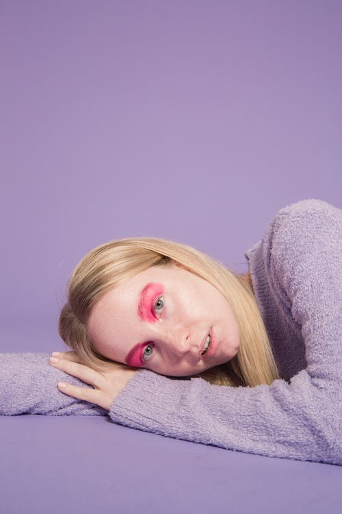 Emotionless woman with colorful makeup lying in studio