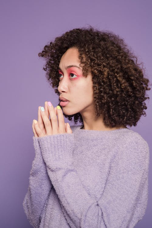 Serious young ethnic woman in sweater with pink makeup on face and manicure with clasped hands in bright studio on purple background