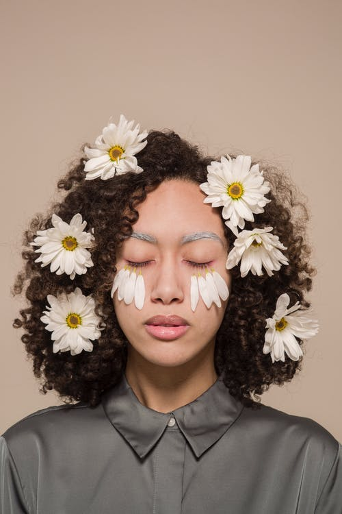 Gentle ethnic woman with chamomile flowers in hair