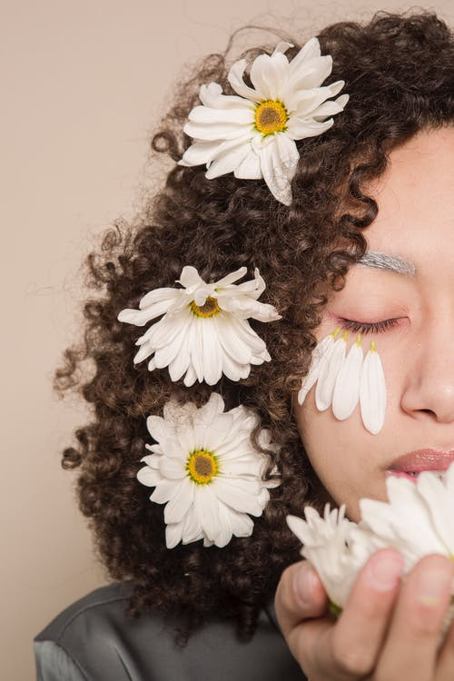 Crop serious young ethnic woman with white daisies in curly hair and hands with petals on cheeks with closed eyes in bright studio on beige background