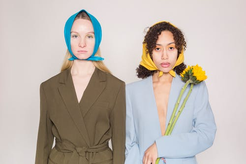 Trendy multiracial female models wearing elegant outfits and colorful headscarves looking at camera while standing against gray background with yellow flower