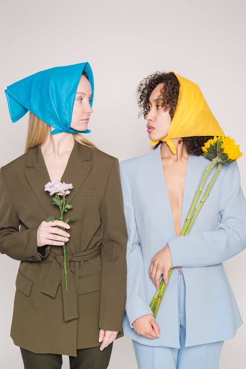 Stylish multiracial female models in trendy clothes wearing colorful headscarves looking at each other while standing against gray background with flowers in hands