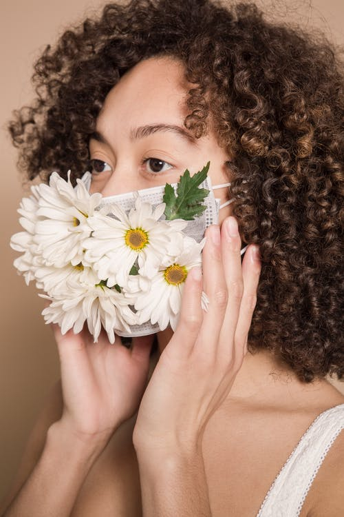 Ethnic female with curly hair wearing mask with chamomile flowers standing against beige background during disease outbreak in modern studio