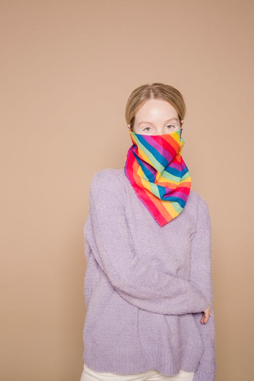 Young female in casual clothes covering mouth with bandana with LGBT rainbow flag and looking at camera against beige background