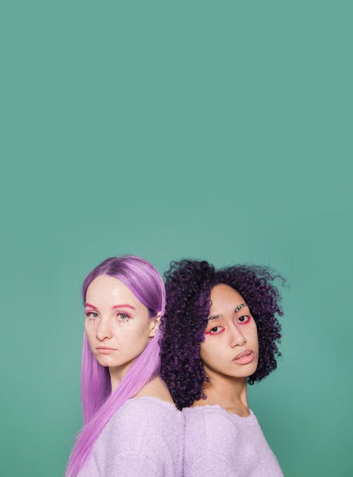 Side view of emotionless young multiracial female models with dyed purple hair standing back to back and looking at camera against green background