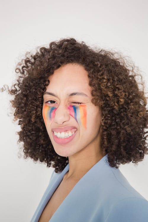 Expressive young ethnic female model with dark curly hair and painted LGBT rainbow flag onnface making grimace and looking at camera against white background