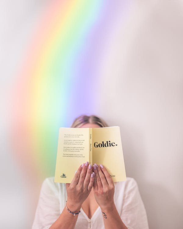 Unrecognizable female reading book in soft cover holding near face and standing near rainbow on background