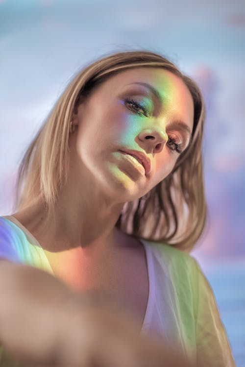 Portrait of charming young blonde female with colorful light on face and body looking at camera