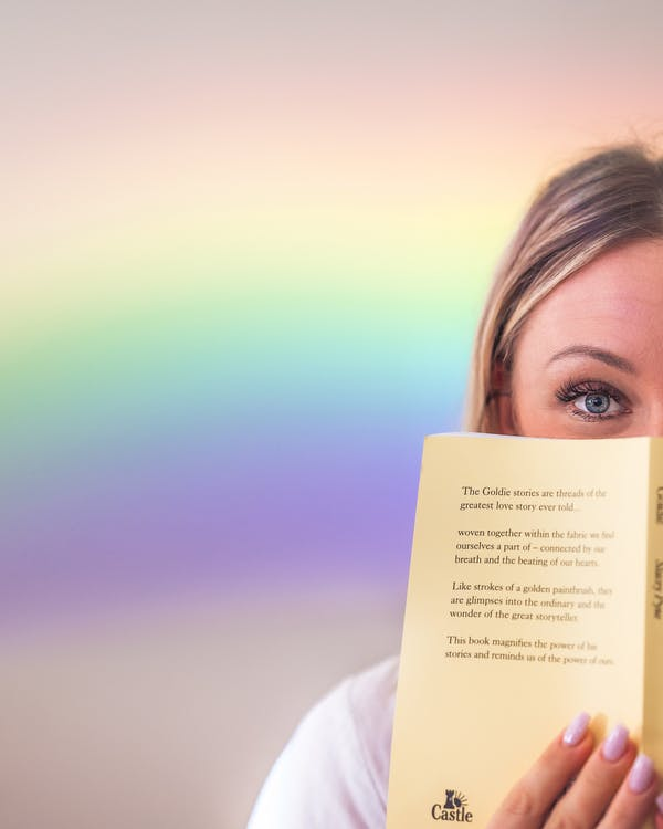 Crop female with blue eyes showing opened book in soft cover and hiding lower face behind novel and standing against bright background with rainbow