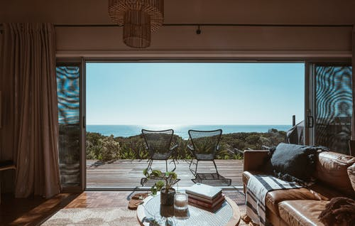Interior design of luxurious apartment with large balcony doors and wooden terrace having picturesque view on green forested seashore and calm blue sea