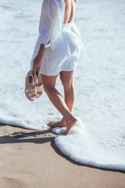 Crop faceless female in light summer outfit standing in foamy waves of ocean surf and holding sandals in hand
