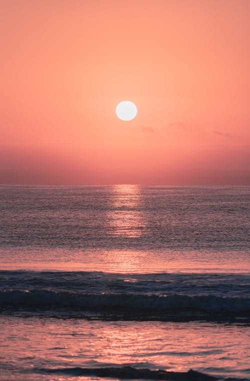 Dramatic red sunset over waving ocean