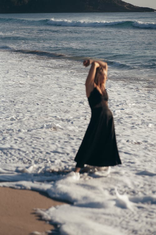 Full length of relaxed female in sundress crossing arms over head and looking away at seaside while spending time on sandy beach during summer vacation