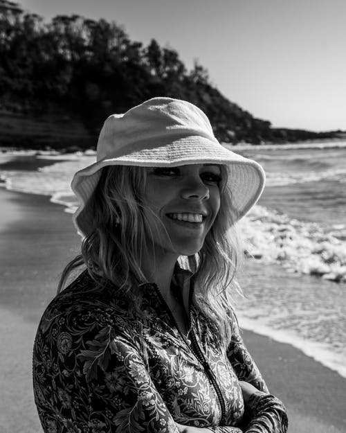 Black and white of smiling female traveler looking at camera while standing on sandy beach near wavy ocean