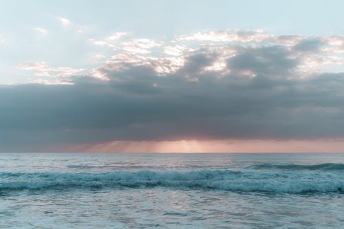 Picturesque seascape with foamy waves washing coast under cloudy colorful sky at sunrise