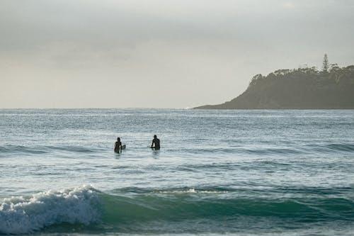 Surfers swimming in rippling ocean in sunlight