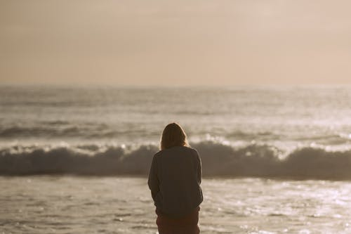 Person standing on shore and admiring wavy ocean in sunlight