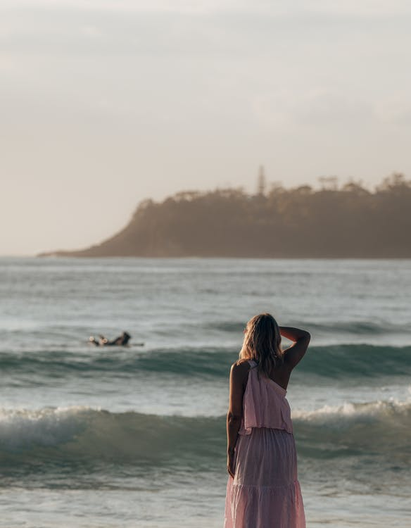 Back view of faceless woman in stylish dress standing on shore while admiring view of waving sea in sunny summer day with hills on background