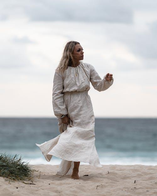 Thoughtful woman walking on beach near sea