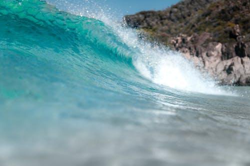 Wavy blue sea near rocky formations on coast