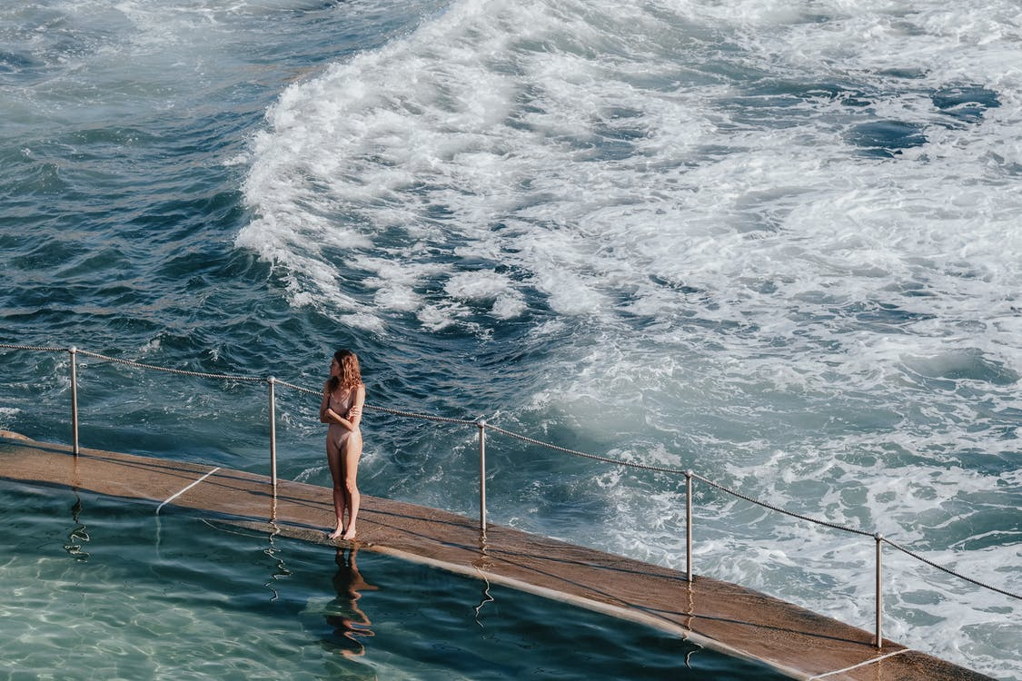 High angle full body of anonymous lady in swimsuit standing on pier with railing near foamy waving sea in sunny summer day
