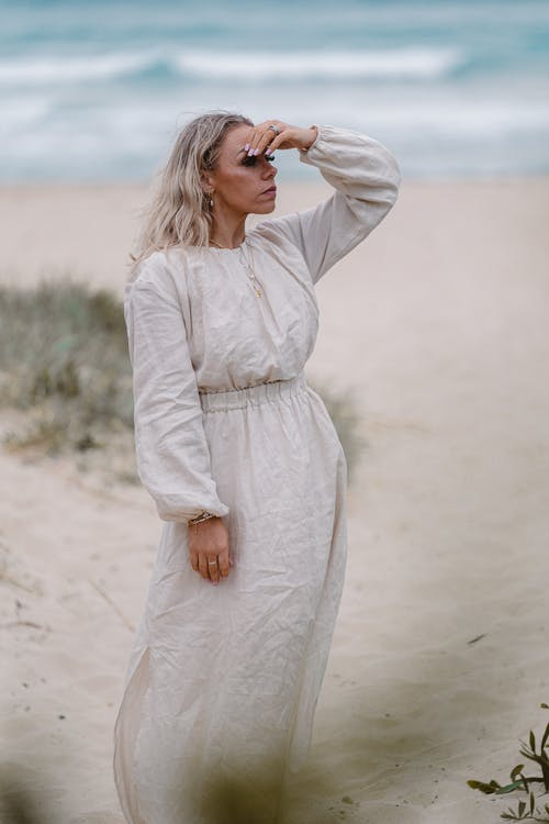 Adult serious female in white dress standing on sandy shore near rippling ocean while admiring view in summer day
