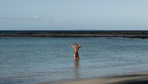 Unrecognizable woman in swimwear standing in ocean