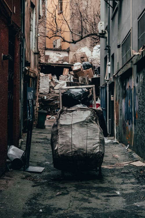 Trolley with trash in dirty alley with pile of rubbish between old shabby buildings