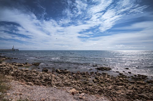 Picturesque sea with stony coast under cloudy sky