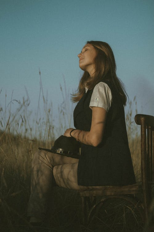Young woman sitting cross legged with closed eyes in field