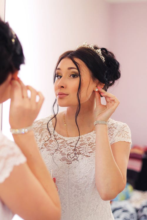 Charming bride with hairstyle with stylish crown in white dress looking at mirror and adjusting earring in light room
