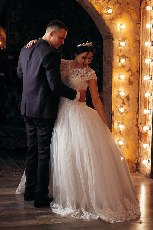 Calm groom in classic suit embracing charming bride in white wedding dress while dancing in dark room with shiny lights