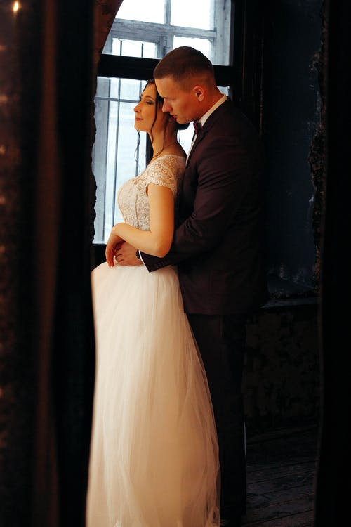 Side view of romantic newlywed couple in stylish wedding clothes standing in dark room and embracing in daylight