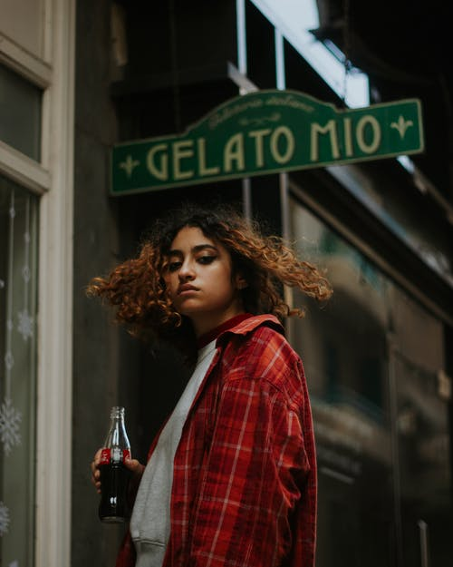 Stylish female standing with glass of soda on street
